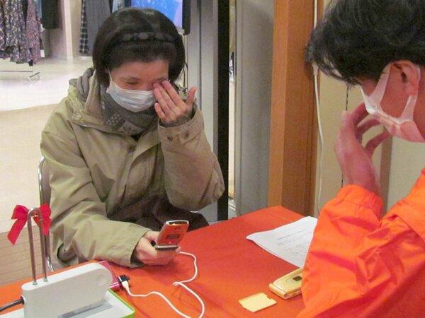 故人のメールを読み返し、目頭を押さえる女性(滋賀県彦根市竹ケ鼻町・ビバシティ平和堂)