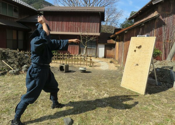 手裏剣投げの技を披露する大介さん。奥の建物が古民家を改修した「蜻蛉館」(福井県若狭町熊川)