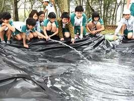 地域住民と造ったビオトープに水を入れる児童たち(大津市・比叡平小)