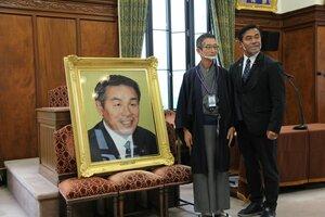 西陣織の肖像画と記念撮影する冨家社長(右から2人目)と馳氏