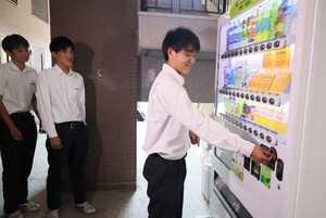 新たに設置された災害救援ベンダーで飲み物を買う生徒(京都市伏見区・京都工学院高)