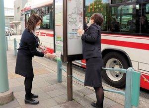 【資料写真】バス停を消毒する定期観光バスのガイド(京都市山科区)