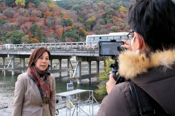 嵐山の渡月橋前でオンラインツアーの撮影に臨む井上さん(左)=2020年12月3日、京都市右京区