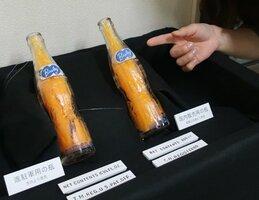 長岡京市内の発掘調査で見つかった進駐軍用のバヤリースの瓶(左)と国内販売用の瓶。一見すると同じに見えるが、陽刻された英字表記が少し違う=長岡京市奥海印寺・市埋蔵文化財センター