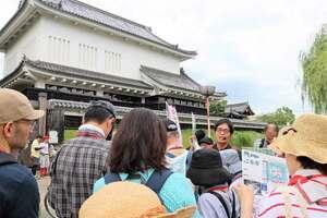 資料を手に持つ梅林さん(中央)の説明を聞く参加者たち=長岡京市勝竜寺・勝竜寺城公園