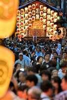 駒形提灯の明かりの下、後祭の宵山を楽しむ人たち(23日午後7時10分、京都市中京区)