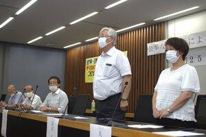 裁判長の交代を切実に訴える(右から)丸山さんと弘次さん=大阪市・大阪弁護士会館