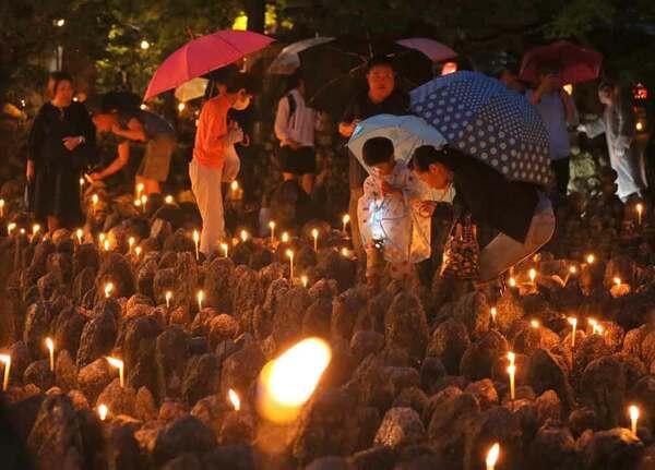 傘を差しながら石仏にろうそくをともし手を合わせる参拝者(23日午後6時53分、京都市右京区・化野念仏寺)