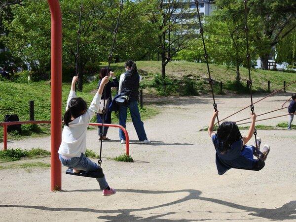 公園で体を動かす小学生と保護者ら。学校の休校延長に「仕方ない」との声が聞かれた(28日、京都市上京区)