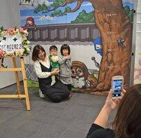 忍者と信楽焼のタヌキが描かれた撮影用ボードの前で写真を撮る家族連れ(甲賀市役所)