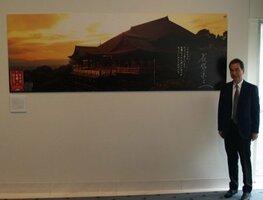 1993年秋の清水寺ポスターを背に「そうだ 京都、行こう。」キャンペーンの25年を振り返る長塚さん(東京都港区南青山)
