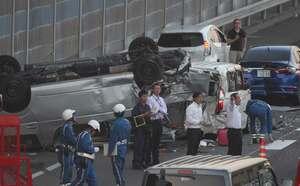 多重衝突の事故現場でひっくり返ってつぶれたワゴン者を調べる警察官(24日午後7時10分、草津市笠山5丁目)