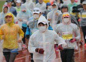 マスク姿でたけびしスタジアム京都をスタートするランナーたち(16日午前9時11分、京都市右京区)