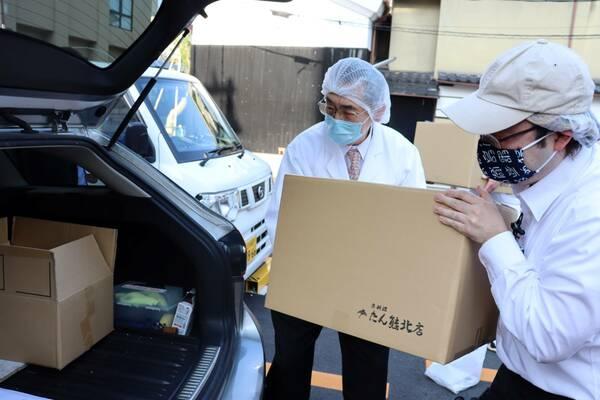 病院に届ける弁当を積み込む加藤さん(右)ら=4月30日、京都市中京区