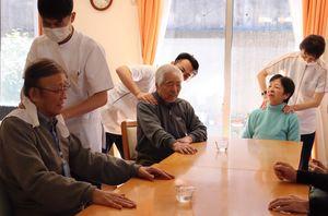 贈られた手作りマスクを着けた整骨院スタッフから、マッサージを受ける高齢者ら(宇治市広野町・デイサービスセンターくりくま)
