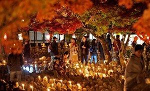 紅葉が彩る境内でろうそくの明かりに照らされる石仏(23日午後6時25分、京都市右京区・化野念仏寺)