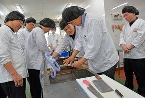 本社内に設置した王将調理道場で、包丁の磨き方を学ぶ「餃子の王将」の副店長ら(京都市山科区・王将フードサービス)