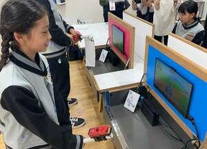 コントローラーをほうきに取り付けてゲームを操作する子ども(兵庫県西宮市・キッザニア甲子園)
