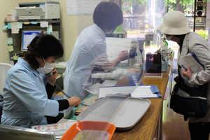 65~74歳のワクチン接種の予約を受け付ける医療機関のスタッフら(10日、京都市北区)