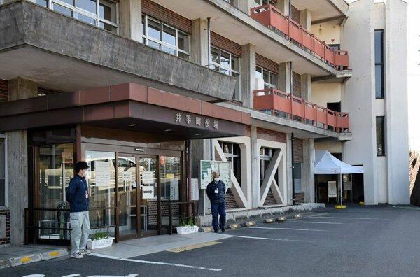 来庁者に右奥の臨時窓口を案内するため、本庁舎前に立つ職員(京都府井手町役場)