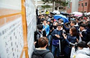 2019年3月にあった京都大の合格発表で掲示板の番号を確認する受験生ら(京都市左京区)