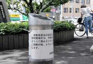 屋外喫煙所の灰皿に張り出された「廃止」の貼り紙。市民の通行も多い(京都府城陽市役所)