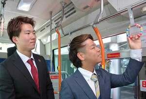 SDGsの認知度アップを目指すつり革の完成を喜ぶ鎌田さん(左)と小猿さん=京都府亀岡市安町・市役所前