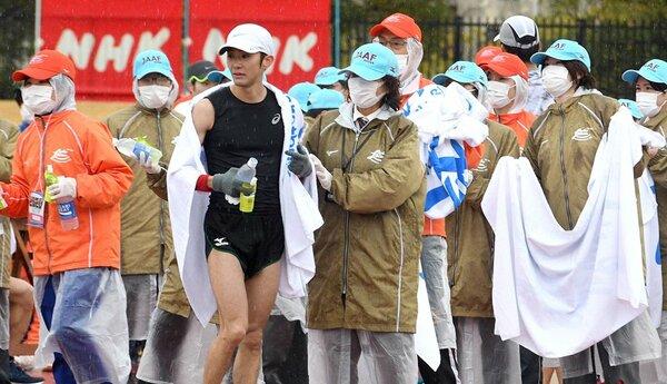 ゴールした選手をマスク姿で誘導する大会スタッフら(8日午前11時53分、大津市・皇子山陸上競技場)