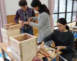 ニホンミツバチ用の巣箱を丁寧に組み立てる参加者たち(南丹市園部町・旧西本梅小)