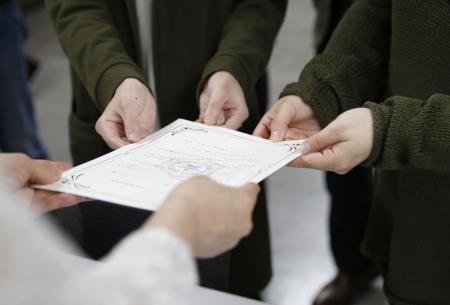 「パートナーシップ宣誓書」の受領証を手にするカップル(奥の2人)=2017年6月、札幌市役所
