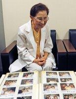 出産直後の家族写真を収めたアルバムを見つめる中部さん(京都市伏見区・中部産婦人科)=画像の一部を加工しています