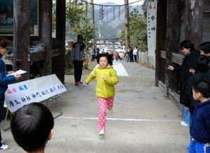 摩気神社の神門を駆け抜ける参加者ら(京都府南丹市園部町)