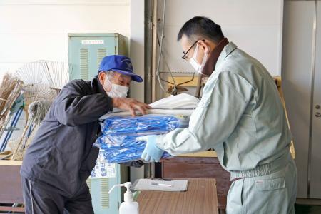 福島県新地町役場で復旧作業に使うブルーシートなどを受け取る男性(左)=20日午前