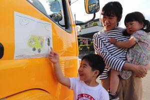 ごみ収集車に貼られた自作の絵を、家族と一緒に見て喜ぶ颯介君(長岡京市長法寺)