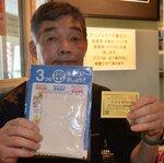 マスクと300円分の食事券を手にする池田さん(南丹市八木町・レストランいけじゅう)