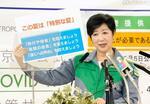 記者会見でボードを掲げ、お盆の帰省や夏休みの旅行などを控えるよう呼び掛ける東京都の小池百合子知事=6日午後、都庁