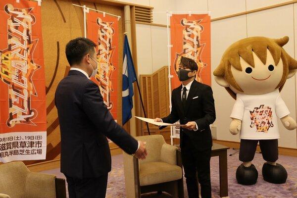 寄付目録を手渡す西川貴教さん(右)=大津市・県公館