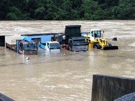 桂川の水位上昇で水に漬かった重機やダンプ類(2018年7月6日、南丹市日吉町)=今井生コン提供