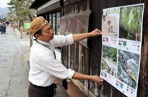 「スイてます嵐山」と呼びかけるポスターを設置する商店主(京都市右京区)