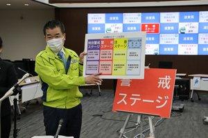 滋賀県内の新型コロナ警戒レベルを「ステージ3(警戒)」へ引き上げることを決め、県民へ感染対策を呼び掛ける三日月知事(15日午前10時3分、大津市・県危機管理センター)