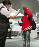 成田空港で搭乗のチェックを受けるウガンダのジュリアス・セチトレコ選手(右)=21日夜