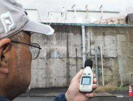 早朝の住宅街で稼働音を計測する。目の前の発電所から響く低音は50デジベルに達した