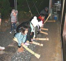 民家の玄関先の地面をわらの束でたたく子どもたち(亀岡市畑野町)
