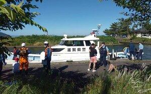 転覆したクルーザーから救助された人たちに話を聞く警察官ら(7日午後4時4分、大津市・近江舞子中浜水泳場付近)