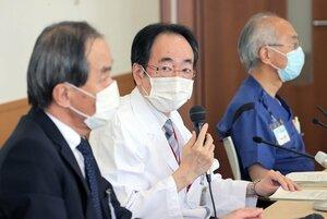 外来診療の見合わせなどの新型コロナウイルス対策について話す京都市立病院の黒田院長(中央)=20日午前11時7分、京都市中京区・市立病院