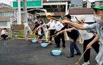 ひしゃくで打ち水をする参加者(京都府長岡京市、市役所仮設駐車場)