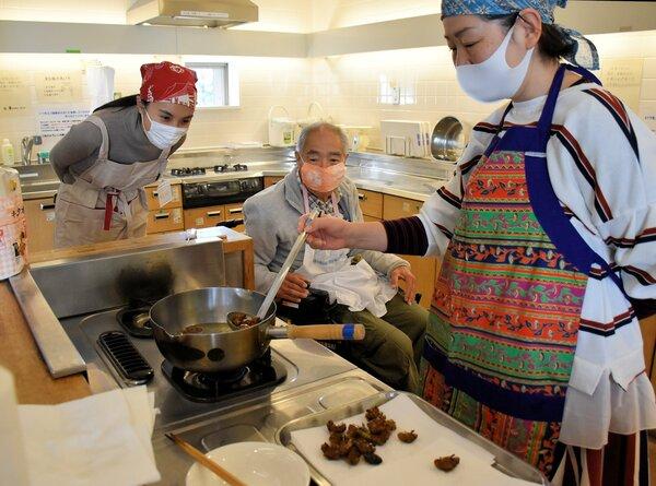 セミの幼虫を油で揚げる参加者たち(京都市伏見区・京エコロジーセンター)