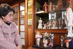 これまでに作った和紙人形を見つめる根本さん(京都府福知山市東中ノ町・根本たばこ店)