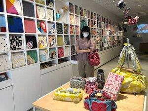店舗の壁にカラフルな風呂敷がずらりと並ぶ。エコバッグとして購入する人が増えているという(京都市中京区・むす美)