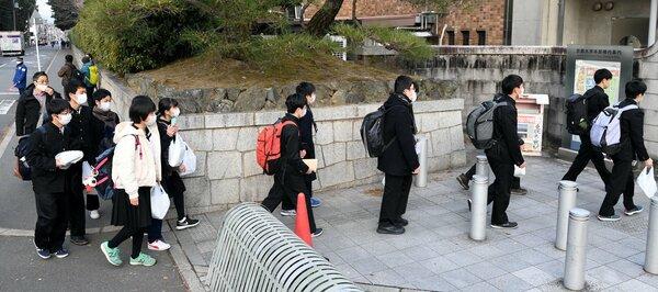 マスク姿で大学入学共通テストの試験会場に向かう受験生たち(16日午前8時18分、京都市左京区・京都大前)